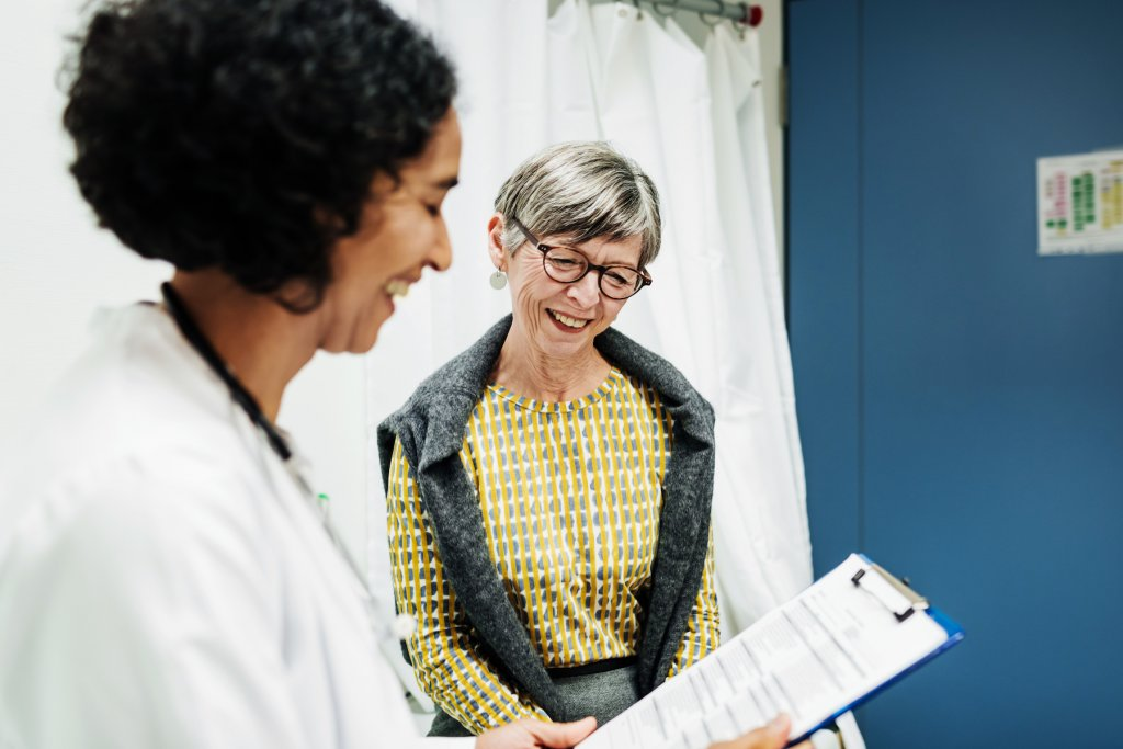 A clinical doctor goes over some test results with an elderly patient at the hospital.