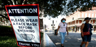 Visitors walk past face mask signs along Decatur Street in the French Quarter on July 14, 2020 in New Orleans, Louisiana.