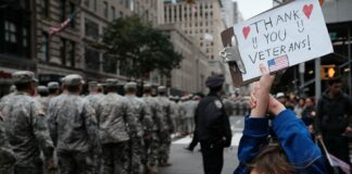 Gavin Kinney (9) holds up a sign thanking veterans at the nation's largest Veterans Day Parade in New York City on November 11, 2015, in New York City.