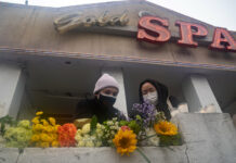 Mourners visit and leave flowers at the site of two shootings at spas across the street from one another, in memorial for the lives lost, on March 17, 2021, in Atlanta, Georgia.
