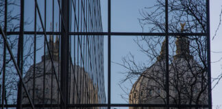 The Idaho State Capitol reflected in the Joe R. Williams building on March 21, 2021.