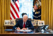 President Biden signs executive actions in the Oval Office.