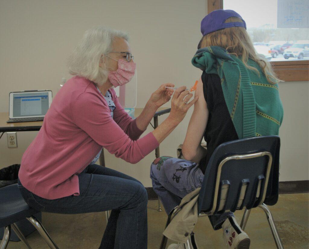 Dr. Laurel Desnick, county health officer in Park County, Montana, administers a covid vaccine to a senior at Park High School.