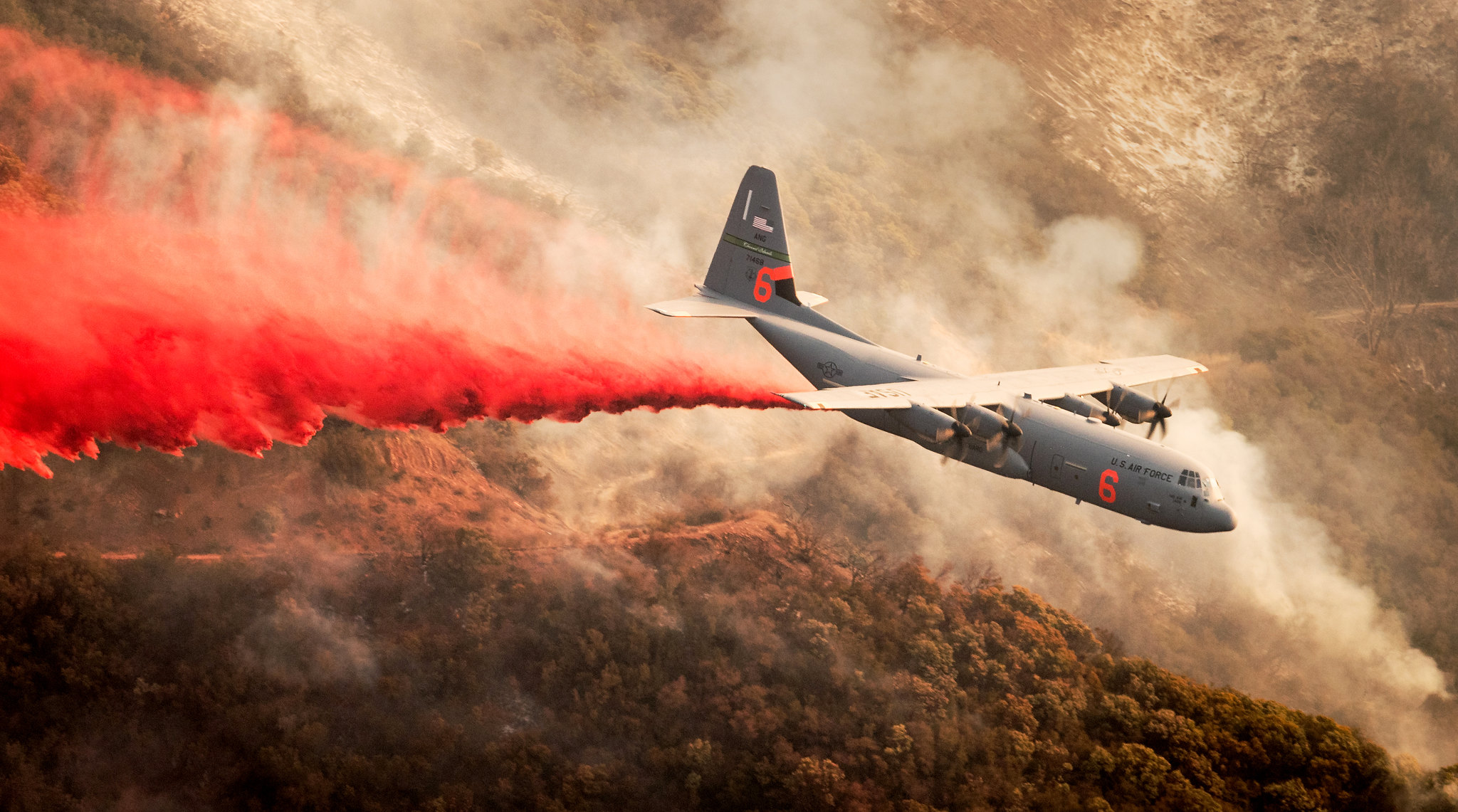 A C-130J Hercules assigned to the 146th Airlift Wing based at Channel Islands Air National Guard Base in Port Hueneme, California, drops fire retardant chemicals onto a ridge line above Santa Barbara, Dec. 13, 2017, as part of the effort to contain the Thomas Fire. (U.S. Air Force photo by J.M. Eddins Jr.)