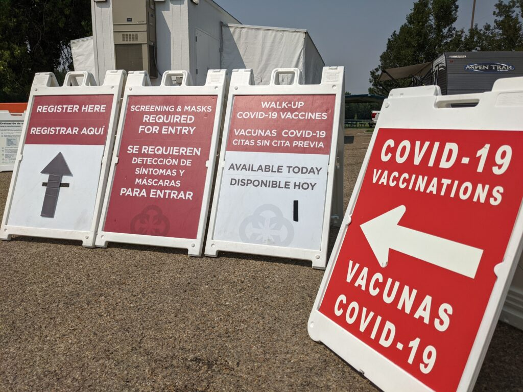 Signs lead people to a COVID-19 vaccination clinic set up at a park in Caldwell.