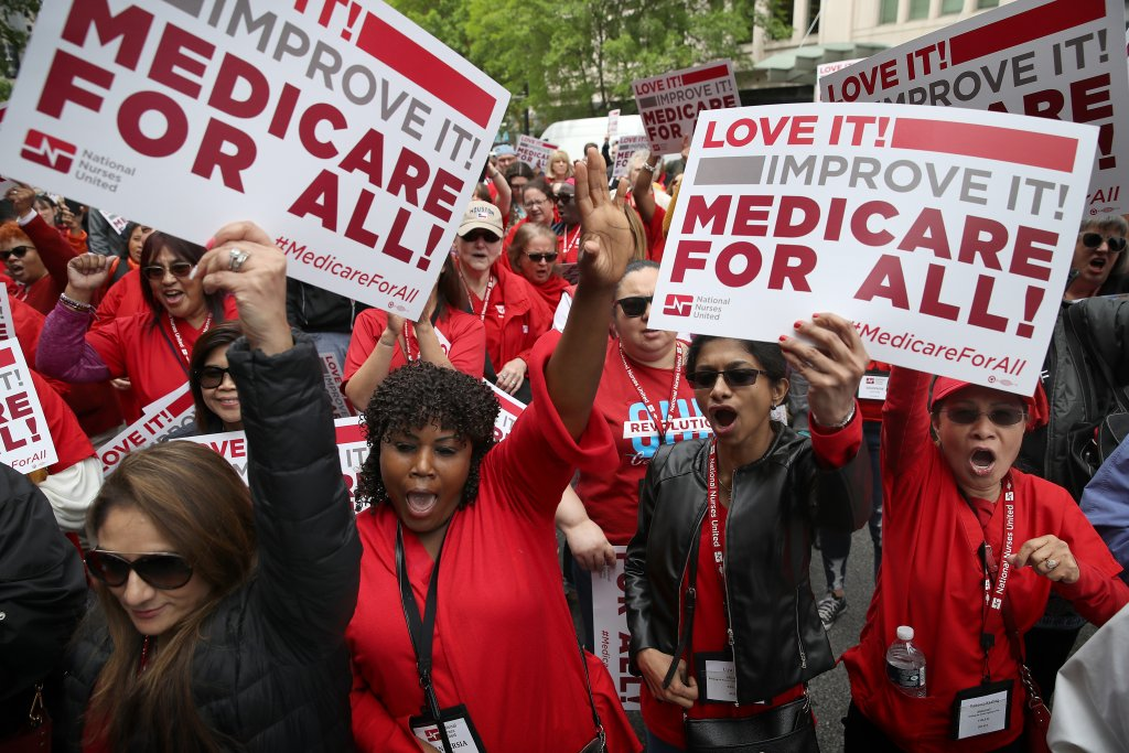"""Protesters supporting """"Medicare for All"""" hold a rally outside PhRMA headquarters in 2019 in Washington, D.C."""