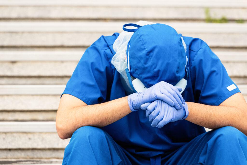an overworked male nurse sits outside hospital
