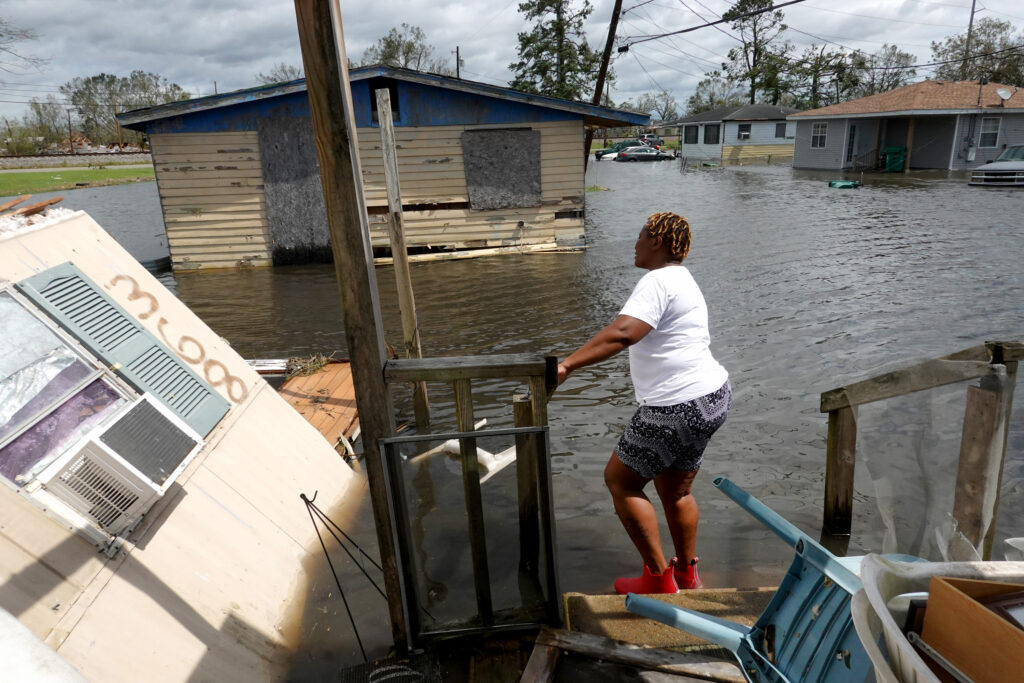 Woman looks at wreckage from Hurricane Ida