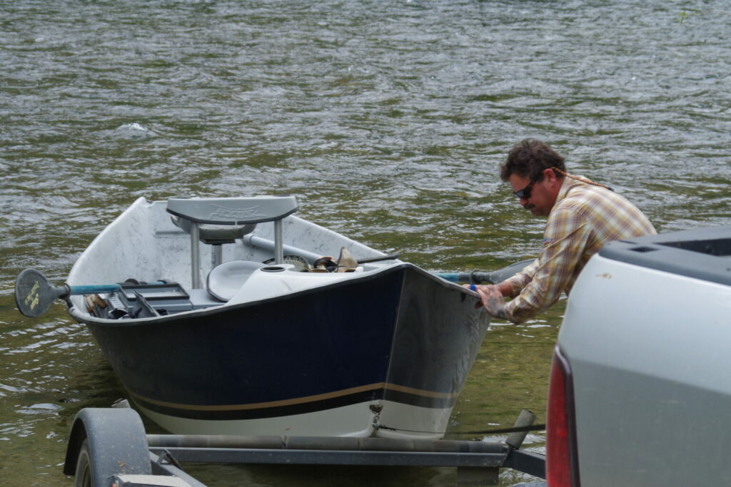An angler launches a drift boat