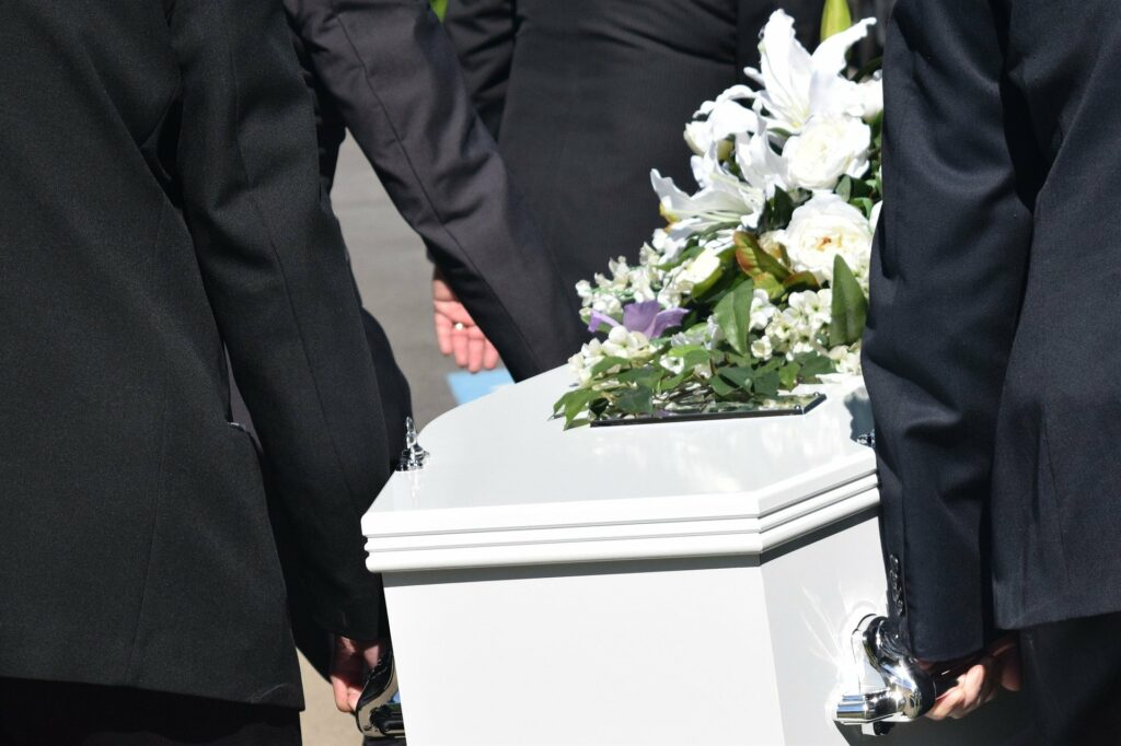 Stock photo of pallbearers carrying a casket with a white flower arrangement