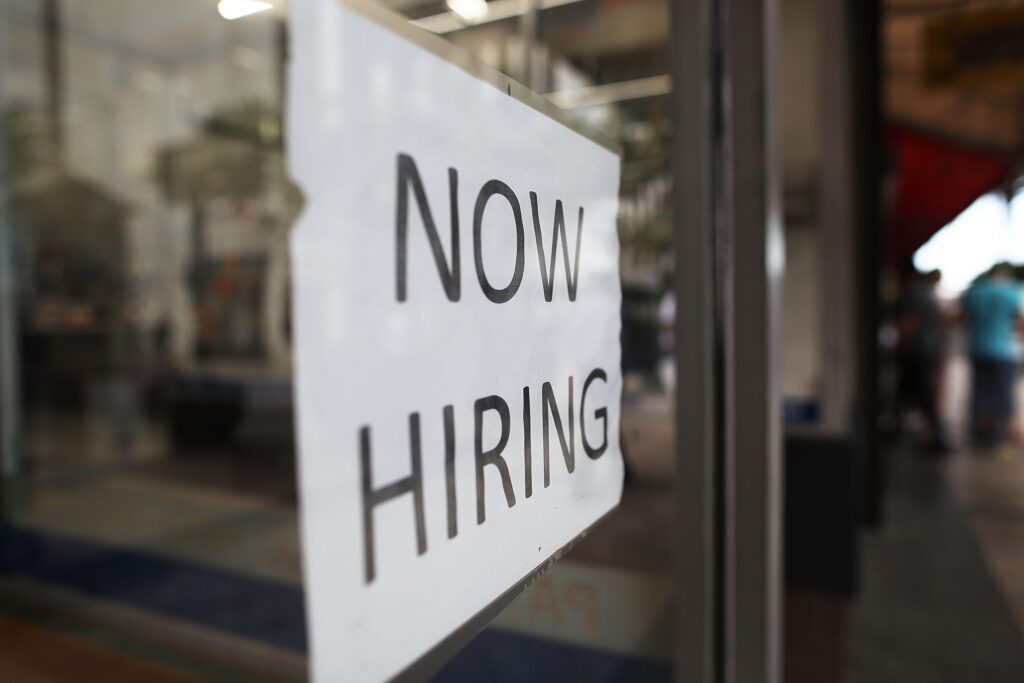 """A sign shows the words """"now hiring"""""""