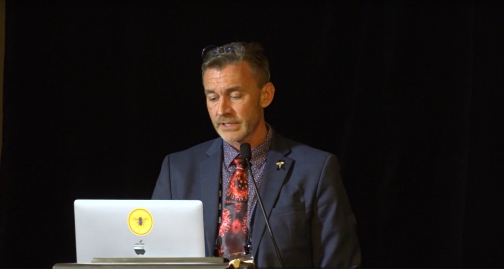 Photo of Dr. Ryan Cole speaking at a conference in early October