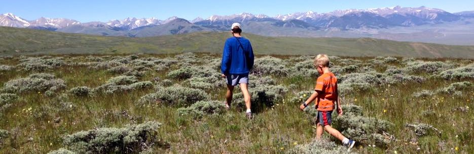 Photo of a man hiking with his son in the Idaho wilderness in springtime